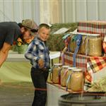 A little boy and man stand next to a grain display at the 2014 Klickitat County Fair.