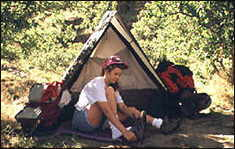 A hiker putting on her shoes in front of a tent.