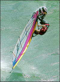 A wind surfer sailing into the air.