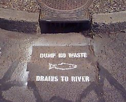 "A storm drain stencil that reads, ""Dump no waste, drains to river."""
