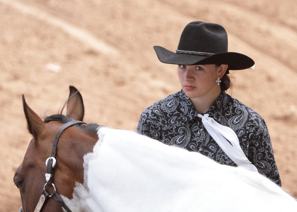 A young woman stands next to her horse in the arena at the 2014 Klickitat County Fair.
