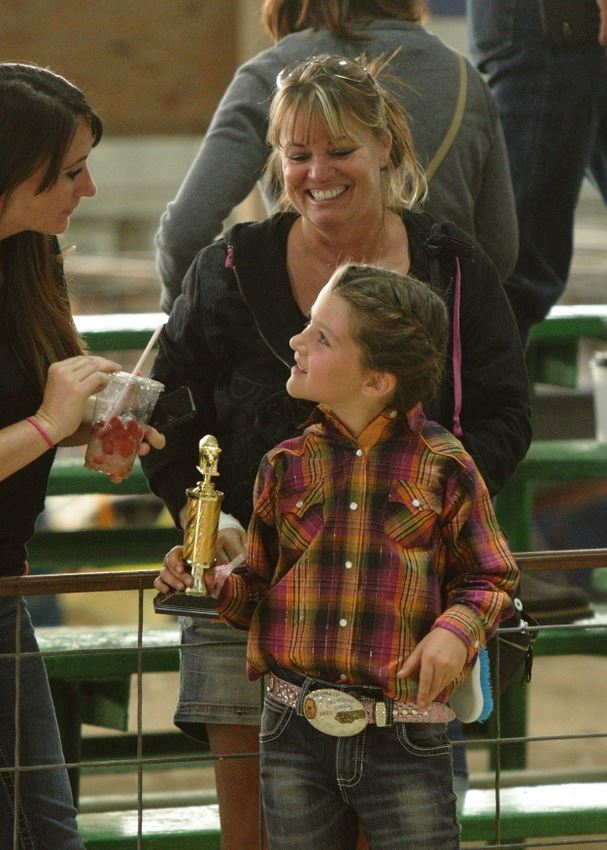 A little girl holds a trophy at the 2014 Klickitat County Fair.