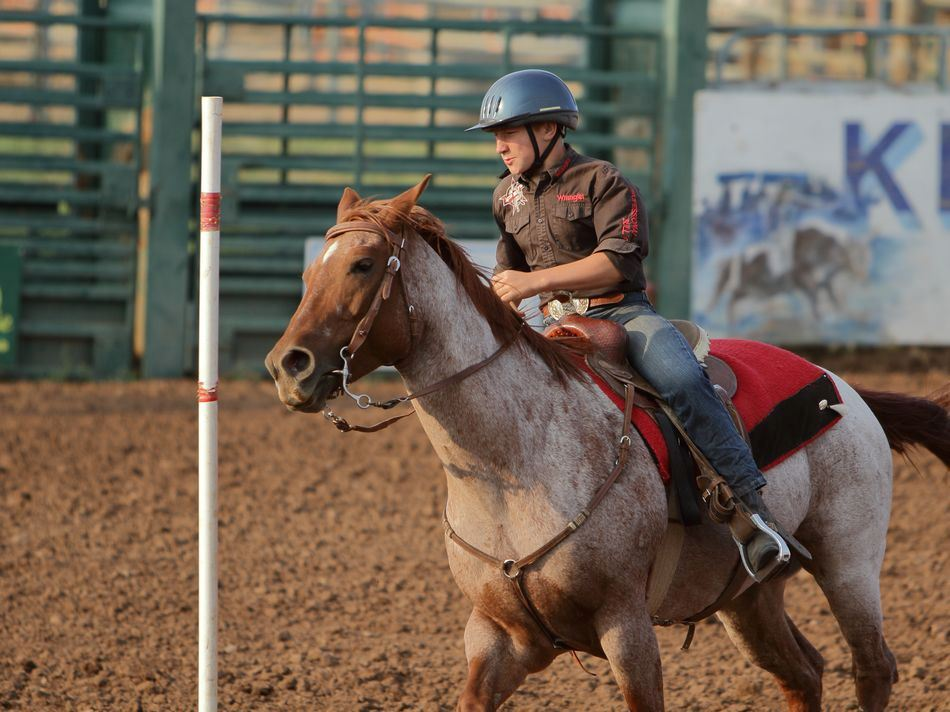 A young man runs his horse around a pole at the 2015 Klickitat County Fair.