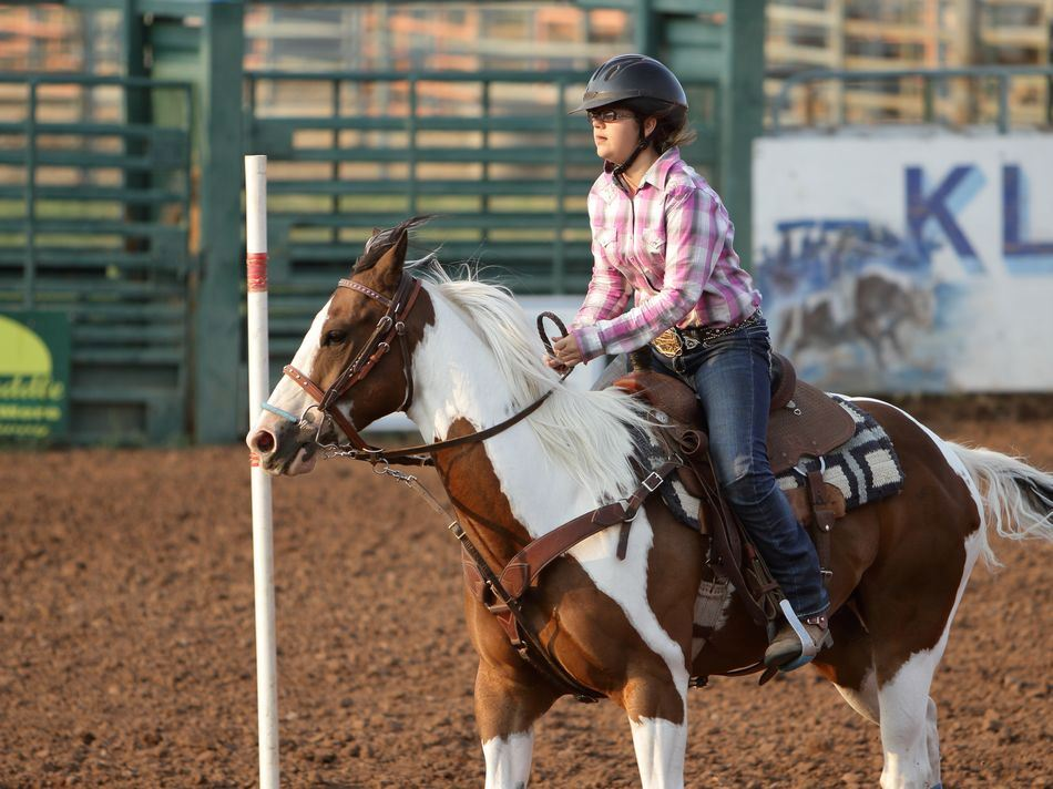 A young woman runs her horse around a pole at the 2015 Klickitat County Fair.