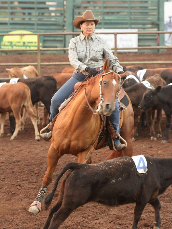 A woman runs her horse to herd a calf at the 2015 Klickitat County Fair.